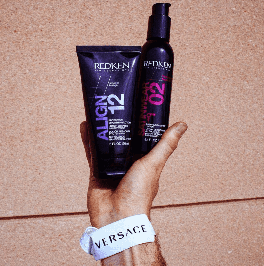 Redken Align 12 and Satinwear 02 being held up by a hand